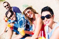 Cuatro amigos que se sientan en la playa del lago con los cócteles Fotos de archivo libres de regalías