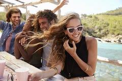 Cuatro amigos que se sientan en una tabla por el mar, manos en el aire imagenes de archivo