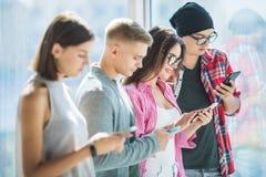 Cuatro amigos que trabajan en la compañía que es adicta de los artilugios, usando los teléfonos y la tableta elegantes para busca fotos de archivo libres de regalías