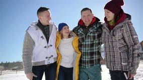 Cuatro amigos se están abrazando en fondo del cielo azul Retrato del primer de dos pares felices durante su invierno metrajes