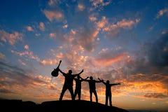 Cuatro amigos siluetean encima de una colina con la guitarra fotografía de archivo