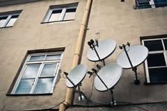 Cuatro antenas en la pared amarillenta imagenes de archivo