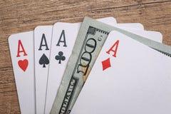 Cuatro as del póker con los billetes de dólar Imágenes de archivo libres de regalías