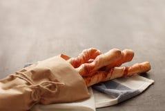 Cuatro baguettes en el papel de embalaje atado con mentira de la guita en la tabla imagenes de archivo