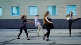 Cuatro bailarines contemporáneos están ensayando danza moderna en una calle delante del edificio en d3ia almacen de video