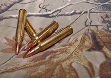 Cuatro balas del rifle con un fondo del camo Imagen de archivo libre de regalías