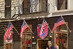 Cuatro banderas americanas que agitan delante de una tienda de souvenirs en New York City Fotos de archivo libres de regalías