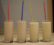 Cuatro batidos de leche en el fondo de la pared azul Imágenes de archivo libres de regalías