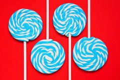 Cuatro blancos y piruletas azules en fondo rojo Imágenes de archivo libres de regalías