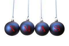 Cuatro bolas azules de la Navidad con las letras de la palabra Navidad Fotografía de archivo
