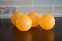 Cuatro bolas plásticas anaranjadas en la tabla del marrón oscuro Foto de archivo