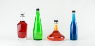 Cuatro botellas de cristal coloridas Imágenes de archivo libres de regalías