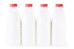 Cuatro botellas de leche con el casquillo rojo aislado Imagenes de archivo