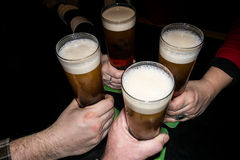 Cuatro brazos del amigo que comen cerveza con espuma Imagenes de archivo