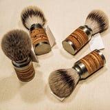 Cuatro brochas de afeitar de madera en la lona imagen de archivo libre de regalías