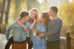Cuatro buenos amigos relajan y se divierten en parque del otoño Imagenes de archivo