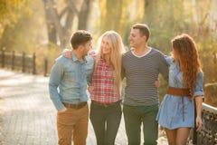 Cuatro buenos amigos relajan y se divierten en parque del otoño Foto de archivo libre de regalías