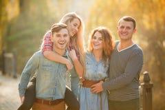 Cuatro buenos amigos relajan y se divierten en parque del otoño Fotos de archivo libres de regalías