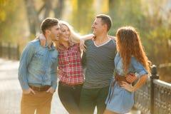 Cuatro buenos amigos relajan y se divierten en parque del otoño Fotografía de archivo
