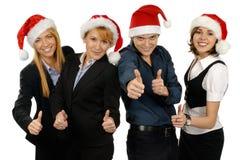 Cuatro businesspersons jovenes en sombreros de la Navidad Imagen de archivo libre de regalías