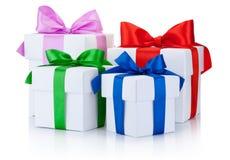 Cuatro cajas blancas atadas con las cintas de satén coloreadas arquean aislado Foto de archivo libre de regalías