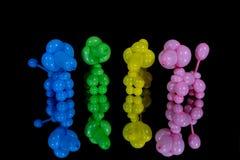 Cuatro caniches coloridos del perro del globo en un espejo Imagen de archivo libre de regalías