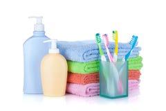 Cuatro cepillos de dientes, botellas de los cosméticos y toallas coloridos Fotos de archivo libres de regalías