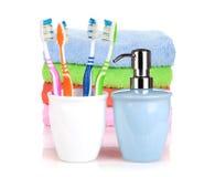 Cuatro cepillos de dientes coloridos, jabón líquido y toallas Fotos de archivo libres de regalías