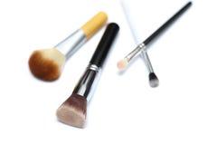 Cuatro cepillos del maquillaje aislados en el fondo blanco imagen de archivo