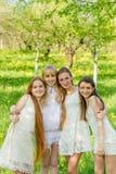 Cuatro chicas jóvenes hermosas en los vestidos blancos en verano Fotografía de archivo libre de regalías