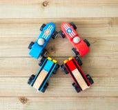 Cuatro coches de carreras del juguete en un fondo de madera visto desde arriba fotos de archivo libres de regalías
