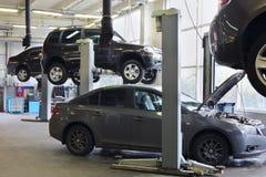 Cuatro coches negros en el garaje Avtomir Imagen de archivo libre de regalías