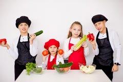 Cuatro cocineros jovenes que van a preparar una ensalada aislada Fotografía de archivo