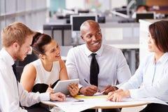 Cuatro colegas de oficina en una reunión casual del equipo Imagen de archivo