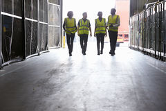 Cuatro colegas en chalecos reflexivos que caminan en un almacén imagenes de archivo
