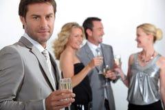 Cuatro colegas que beben el champán Foto de archivo libre de regalías