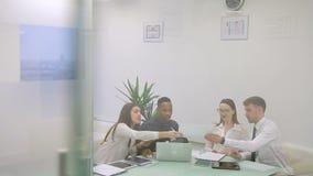 Cuatro colegas trabajan en el informe en sitio de co-trabajo odern brillante almacen de metraje de vídeo
