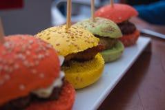 Cuatro coloridos y mini hamburguesas foto de archivo libre de regalías