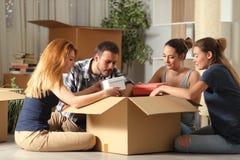 Cuatro compañeros de cuarto unboxing el hogar móvil de las pertenencia fotografía de archivo libre de regalías