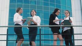 Cuatro compañeros de trabajo femeninos atractivos que se colocan al aire libre y que charlan almacen de metraje de vídeo
