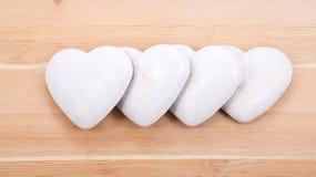 Cuatro corazones del pan de jengibre en fondo de madera Imagen de archivo libre de regalías