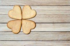 Cuatro corazones del pan de jengibre en una tabla de madera Foto de archivo libre de regalías