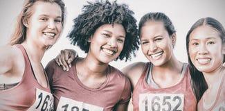 Cuatro corredores sonrientes que apoyan maratón del cáncer de pecho fotografía de archivo libre de regalías