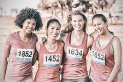 Cuatro corredores sonrientes que apoyan maratón del cáncer de pecho fotos de archivo libres de regalías