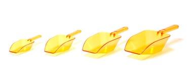 Cuatro cucharadas transparentes plásticas anaranjadas Imágenes de archivo libres de regalías