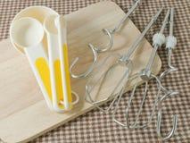 Cuatro cucharas dosificadoras y batir plásticos del metal Imagenes de archivo