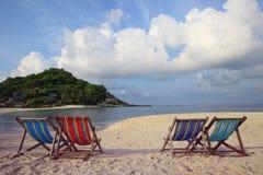 Cuatro de la playa de las sillas en la cara de mar Fotografía de archivo libre de regalías