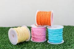 Cuatro del hilo colorido en hierba con el fondo blanco Fotos de archivo