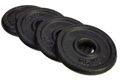 Cuatro discos negros del metal para las pesas de gimnasia Imágenes de archivo libres de regalías