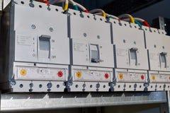 Cuatro disyuntores de poder se fijan en el gabinete eléctrico en línea imagenes de archivo
